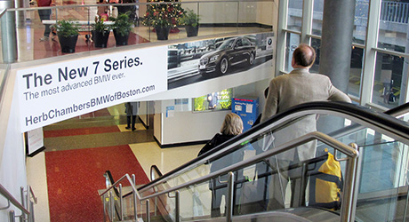A local BMW dealership ad greets travelers as they ride the escalator in an airport.